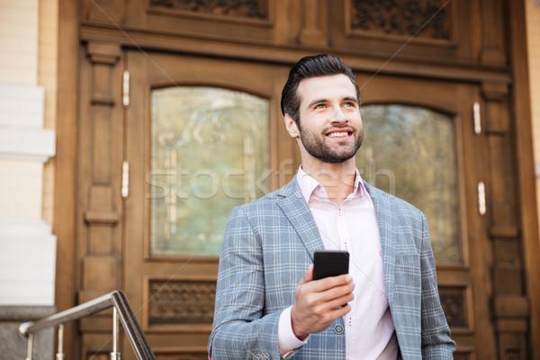 Retrato joven chaqueta teléfono móvil sonriendo Foto stock © deandrobot