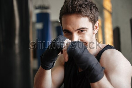 Close up  view of smiling boxer doing exercise in gym Stock photo © deandrobot