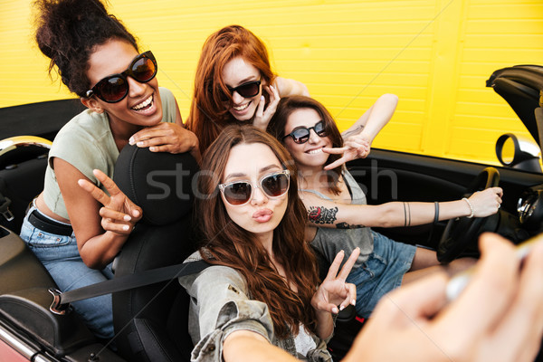Smiling emotional four young women friends sitting in car Stock photo © deandrobot