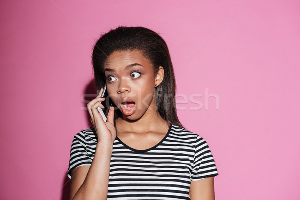 Portrait of a shocked african woman talking on mobile phone Stock photo © deandrobot