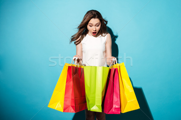 Portrait of a pretty young woman shopaholic with colorful bags Stock photo © deandrobot