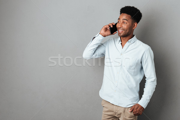 Attractive young african man speaking on mobile phone Stock photo © deandrobot