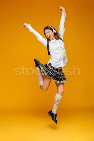 Full length portrait of a joyful teenage schoolgirl Stock photo © deandrobot