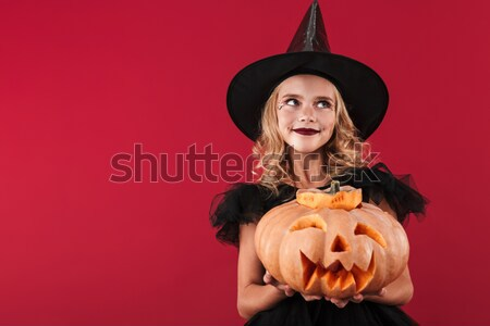 Screaming woman in halloween costume holding curved pumpkin Stock photo © deandrobot