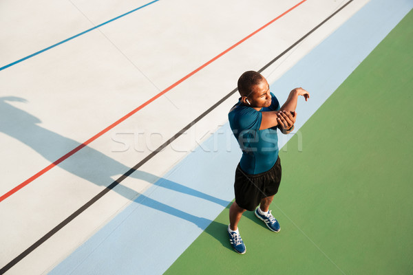 Top view portrait of a young african sportsman stretching Stock photo © deandrobot