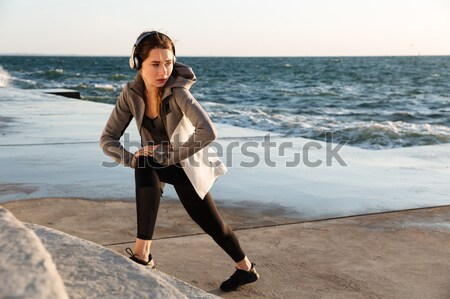 Young pretty sport woman with headphones doing stretch exercise  Stock photo © deandrobot
