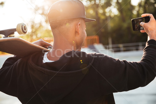 Stock photo: Back view of a young african man taking a selfie