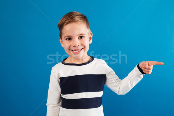 Smiling young boy in sweater pointing away Stock photo © deandrobot
