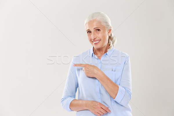 Cheerful old lady in blue shirt, pointing with finger on the emp Stock photo © deandrobot