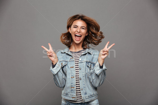 Close-up of overjoyed charming brunette woman showing peace gest Stock photo © deandrobot
