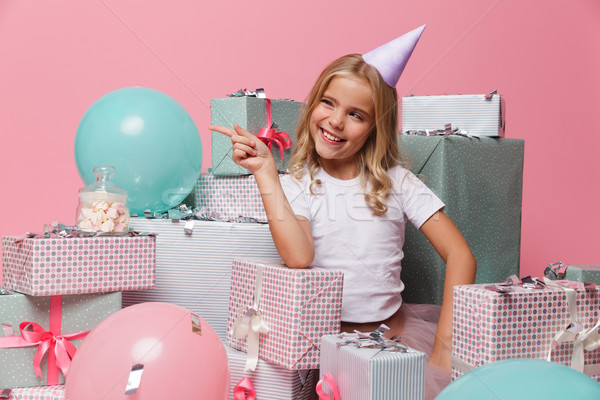 Portrait of a playful little girl in a birthday hat Stock photo © deandrobot