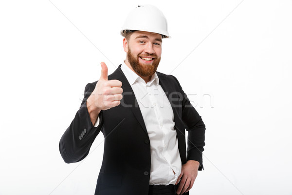 Smiling bearded business man in protective helmet showing thumb up Stock photo © deandrobot