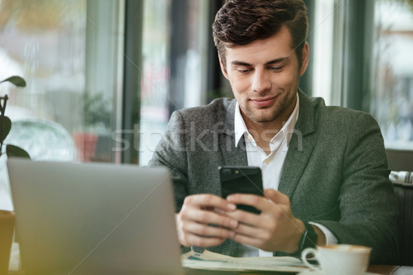 Pleased business man sitting by the table in cafe Stock photo © deandrobot
