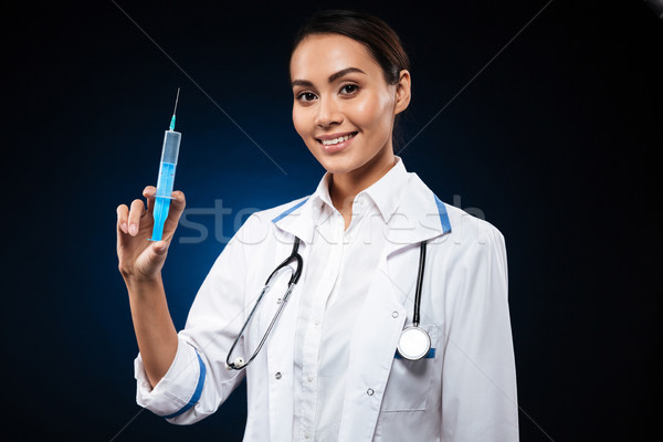 Smiling lady holding syringe and looking camera isolated Stock photo © deandrobot