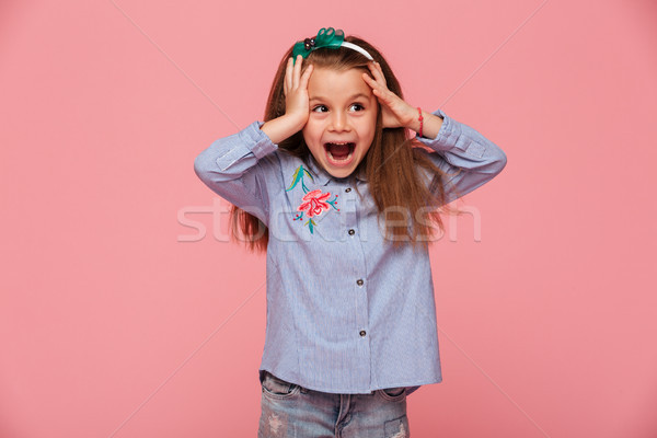 Beautiful little girl reacting emotionally grabbing head with bo Stock photo © deandrobot