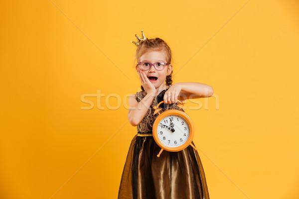 Shocked little girl child holding clock alarm. Stock photo © deandrobot
