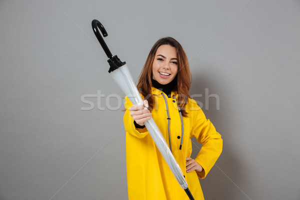 Portrait of a cheerful girl dressed in raincoat Stock photo © deandrobot