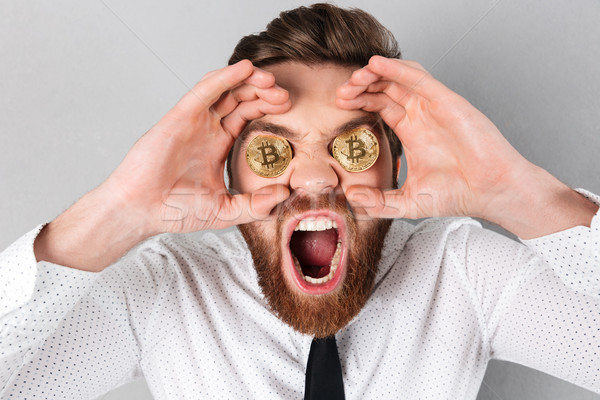 Close up of a mad businessman with bitcoins in his eyes Stock photo © deandrobot