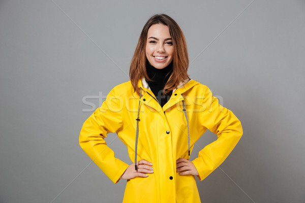 Portrait of a happy girl dressed in raincoat Stock photo © deandrobot