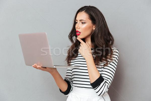 Retrato pensativo mujer mirando ordenador portátil Foto stock © deandrobot