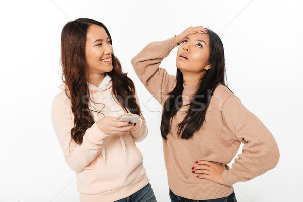 Asian girl displeased because of her sister Stock photo © deandrobot