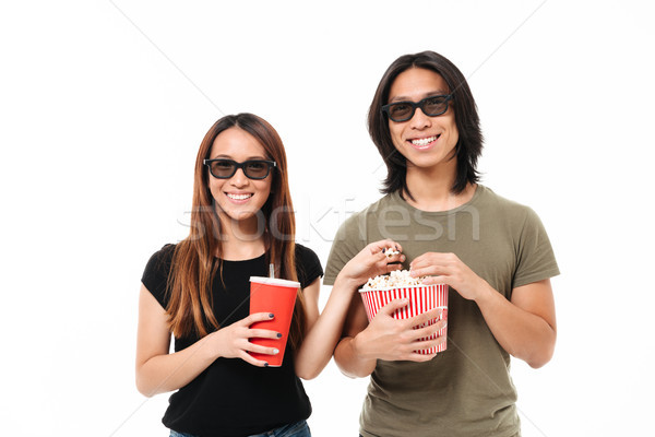 Portrait of a smiling young asian couple in 3d glasses Stock photo © deandrobot