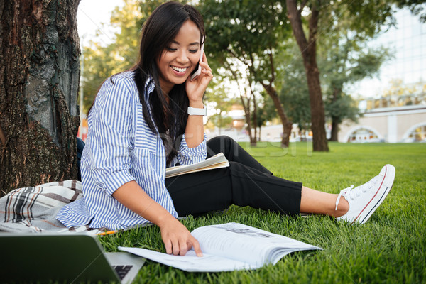 Laughing asian student in striped shirt talking on mobile phone, Stock photo © deandrobot