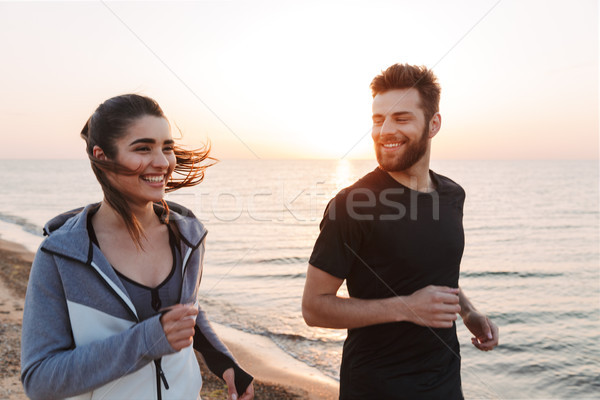 Happy young couple jogging together on a beach Stock photo © deandrobot