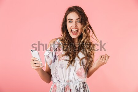 Portrait of a cheerful young girl holding mobile phone Stock photo © deandrobot