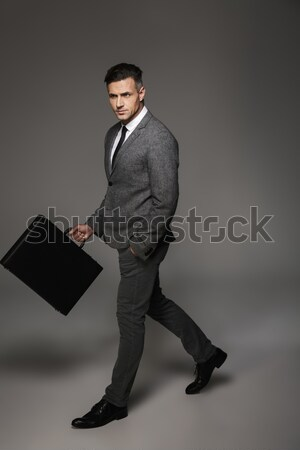 Full-length portrait of a businessman standing with laptop over gray background Stock photo © deandrobot
