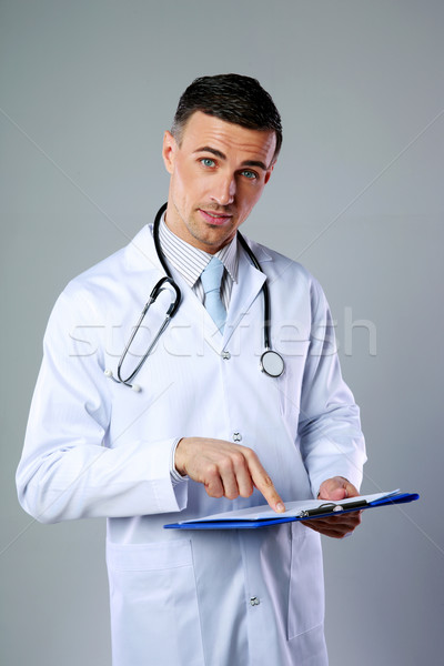 Male doctor telling diagnosis and showing on clipboard on gray background Stock photo © deandrobot