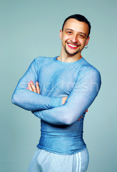 Portrait of a smiling sport man with arms folded on gray background Stock photo © deandrobot