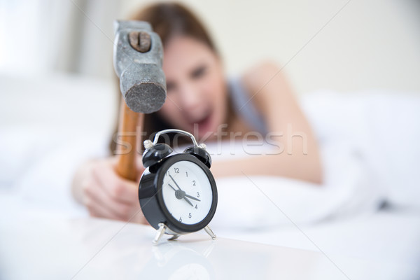 Stock photo: Woman not wanting to get up, taking a hammer to her alarm clock. Focus on clock