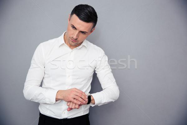 Portrait of a pensive businessman with wristwatch Stock photo © deandrobot