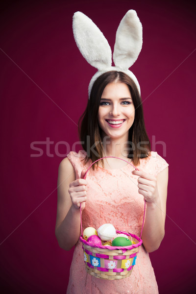 Smiling beautiful woman with an Easter egg basket Stock photo © deandrobot