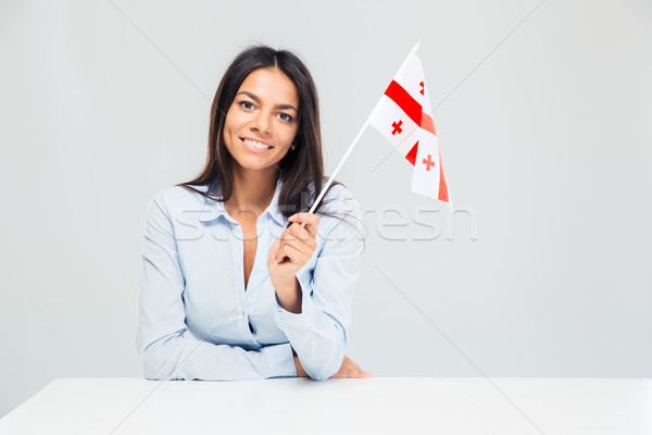 Businesswoman sitting at the table with georgian flag Stock photo © deandrobot