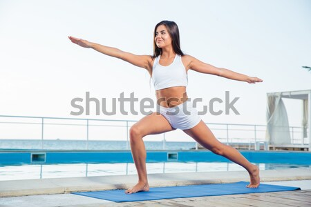Woman doing stretching exercises on yoga mat  Stock photo © deandrobot