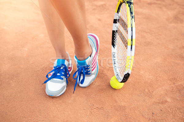Female legs with tennis racket Stock photo © deandrobot