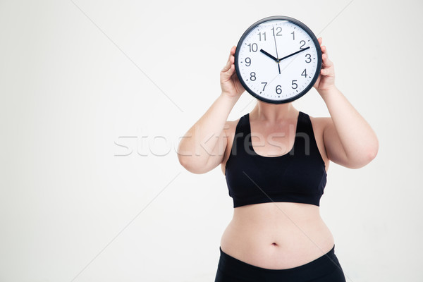 Fat woman covering her face with wall clock Stock photo © deandrobot