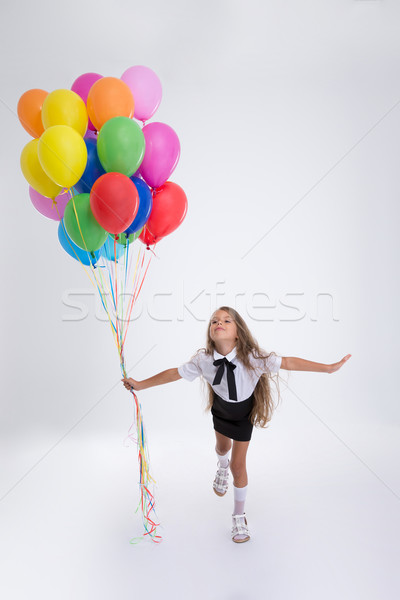 Little school girl standing with balloons Stock photo © deandrobot