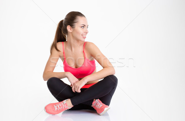 Happy fitness woman sitting with folded legs and looking away Stock photo © deandrobot