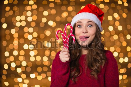 Smiling happy young woman talking on smartphone over sparkling background Stock photo © deandrobot