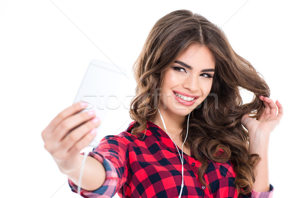 Cheerful attractive young woman smiling and taking selfie Stock photo © deandrobot