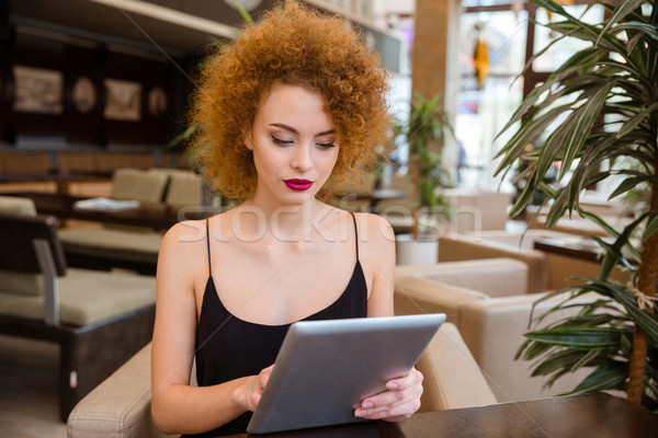 Redhead woman using tablet computer in restaurant Stock photo © deandrobot