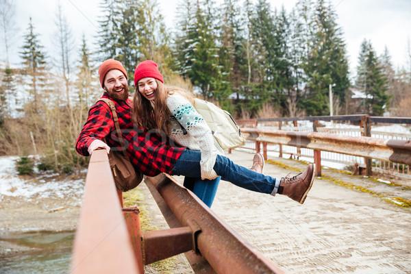 Couple sitting on old bridge and having fun Stock photo © deandrobot