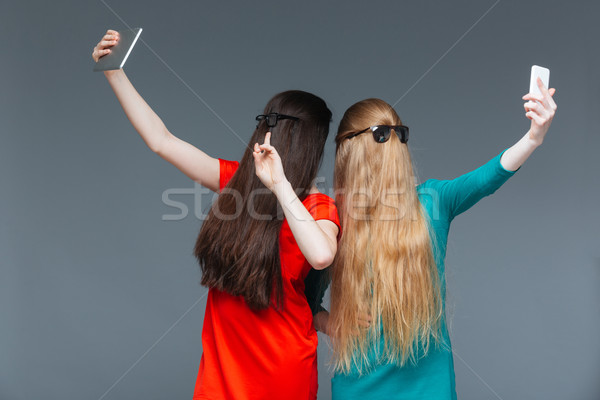 Two women covered face with long hair and taking selfie Stock photo © deandrobot
