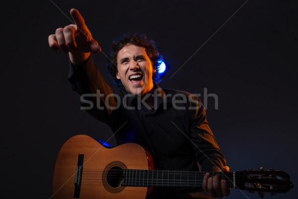 Alegre hombre guitarra senalando dedo feliz Foto stock © deandrobot