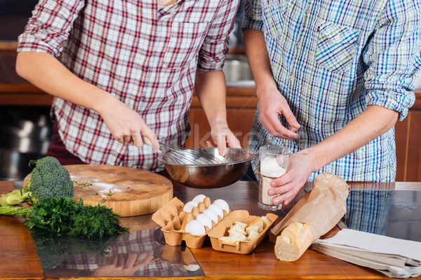 Stock photo: Hands of couple beating eggs and cooking together on kitchen