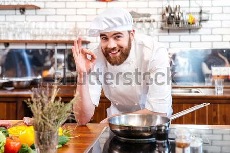 Concentrated chef cook cooking salmon steak on frying pan  Stock photo © deandrobot
