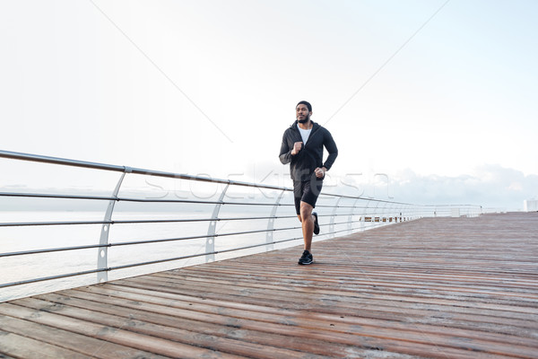 Concentrated african sportsman running on pier in the morning Stock photo © deandrobot